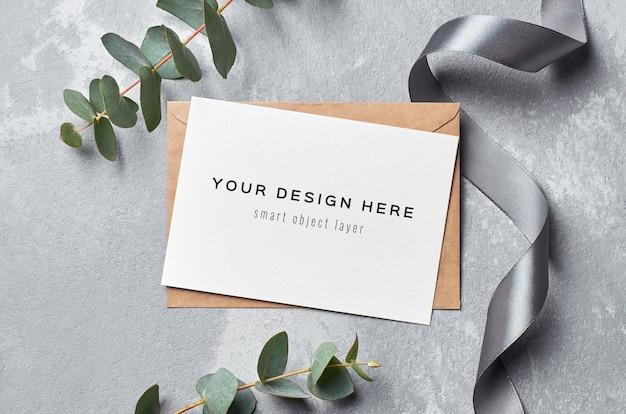 Mockup di biglietto di auguri con busta, nastro d'argento e ramoscello di eucalipto su grigio Psd Premium