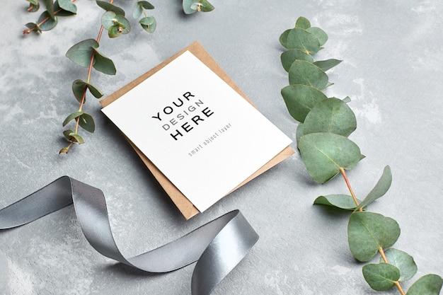 Mockup di biglietto di auguri con busta, nastro d'argento e ramoscello di eucalipto su grigio