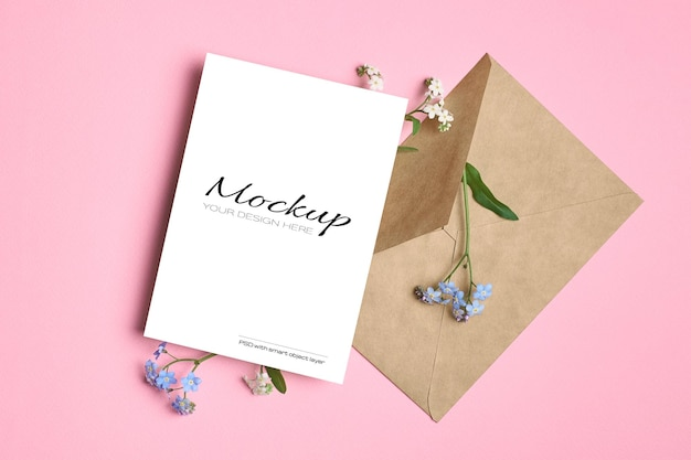 Mockup di biglietto di auguri con busta e fiori blu primaverili del nontiscordardime