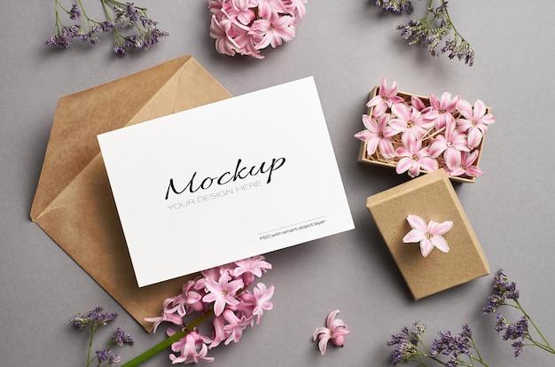 Mockup di biglietto di auguri con busta e fiori rosa primaverili in scatola
