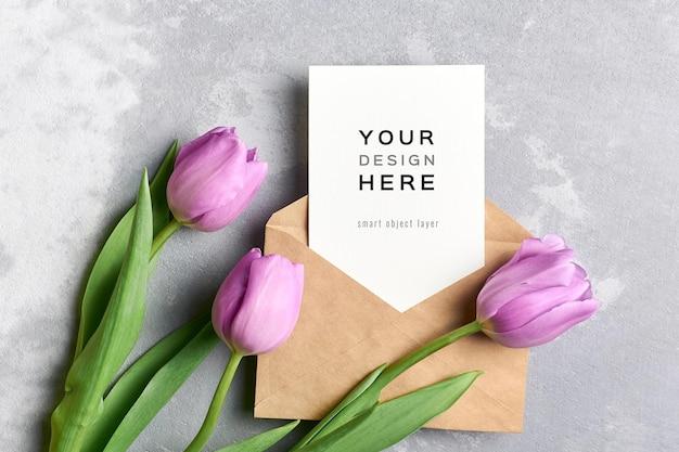 Mockup di biglietto di auguri con busta e fiori di tulipano su grigio