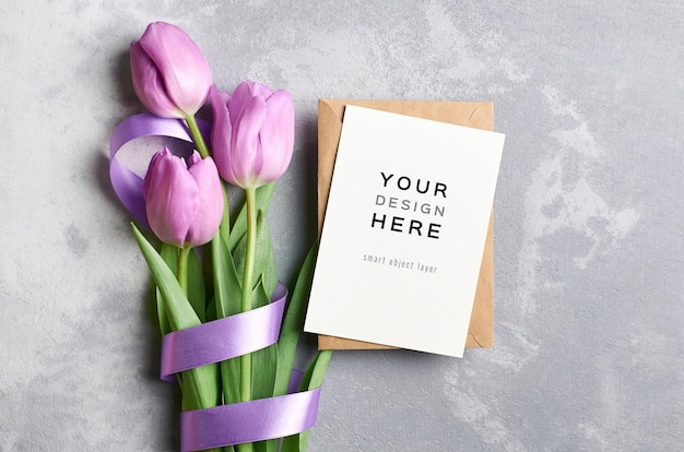 Mockup di biglietto di auguri con busta e fiori di tulipano legati con nastro