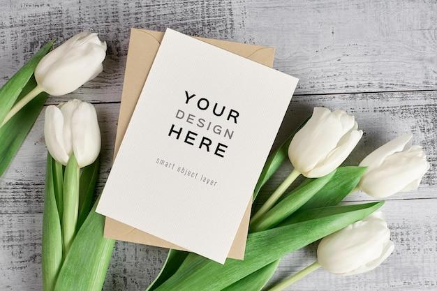 Mockup di biglietto di auguri con busta e fiori di tulipano su legno