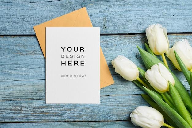 Mockup di biglietto di auguri con busta e fiori di tulipano