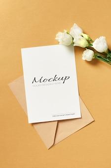 Mockup di biglietto di auguri con busta e fiori di eustoma bianchi su oro