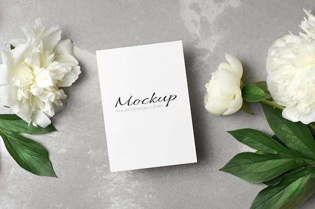 Modello di biglietto di auguri con busta e fiori di peonia bianca su grigio