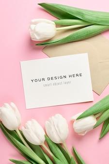 Mockup di biglietto di auguri con busta e fiori di tulipano bianco su sfondo rosa