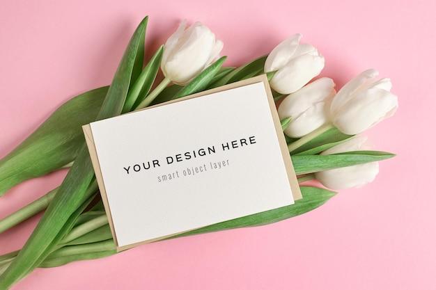 Mockup di biglietto di auguri con busta e fiori di tulipano bianco