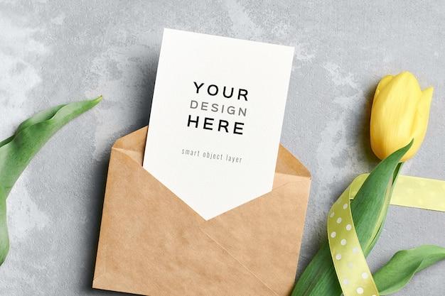 Mockup di biglietto di auguri con busta e fiore di tulipano giallo Psd Premium