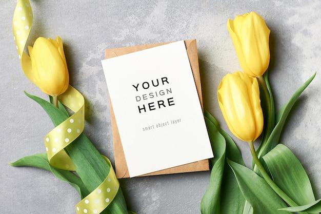 Mockup di biglietto di auguri con busta e fiori di tulipano giallo su grigio