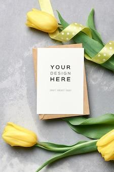 Mockup di biglietto di auguri con busta e fiori di tulipano giallo su grigio Psd Premium