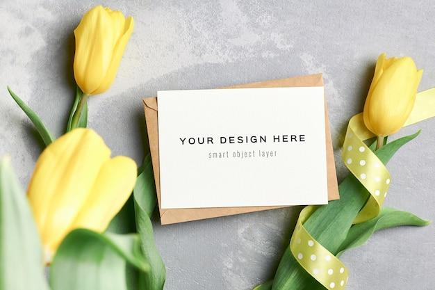 Mockup di biglietto di auguri con busta e fiori di tulipano giallo
