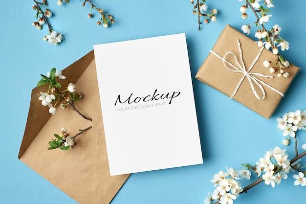 Mockup di biglietto di auguri con scatola regalo, busta e ramoscelli di ciliegio con fiori