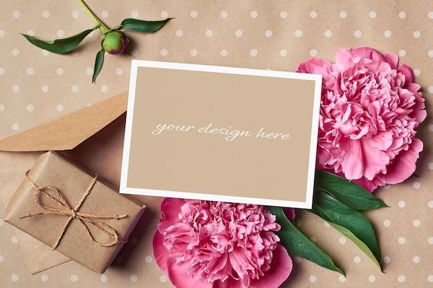 Modello di biglietto di auguri con scatola regalo, busta e fiori di peonia rosa su sfondo di carta artigianale