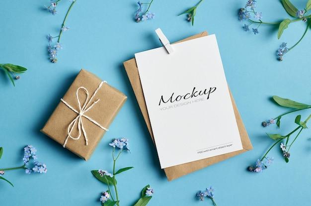 Mockup di biglietto di auguri con confezione regalo, busta e fiori primaverili del nontiscordardime