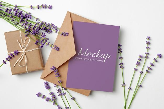 Modello di biglietto di auguri con confezione regalo e fiori di lavanda freschi su bianco
