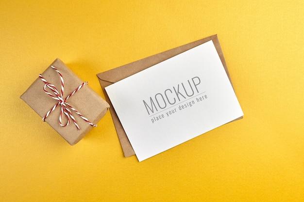 Mockup di biglietto di auguri con confezione regalo su sfondo di carta oro
