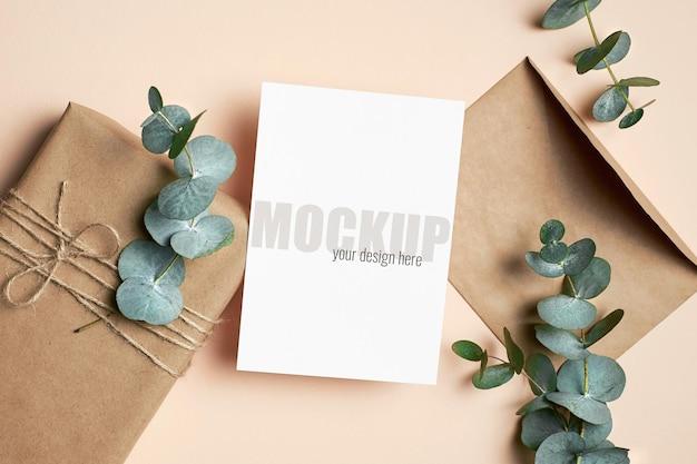 Modello di biglietto di auguri con confezione regalo e ramoscelli di eucalipto verde
