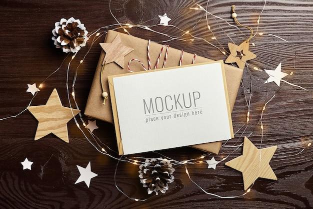 Mockup di biglietto di auguri con confezione regalo, pigne, decorazioni in legno e luci natalizie