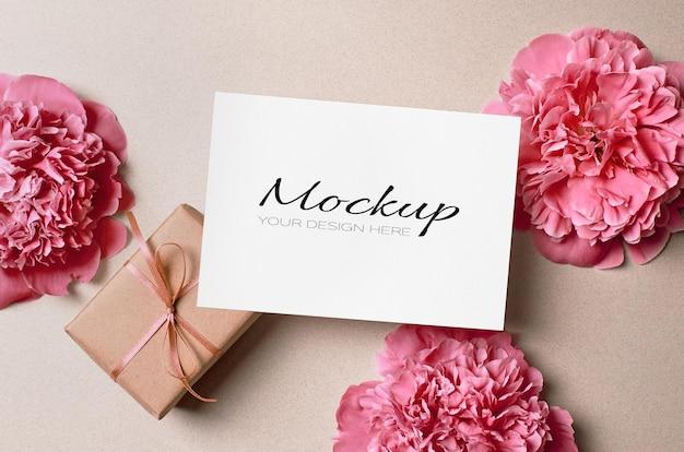 Modello di biglietto di auguri con confezione regalo e fiori di peonia rosa