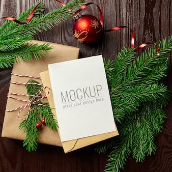 Mockup di biglietto di auguri con confezione regalo, palla di natale rossa e rami di abete
