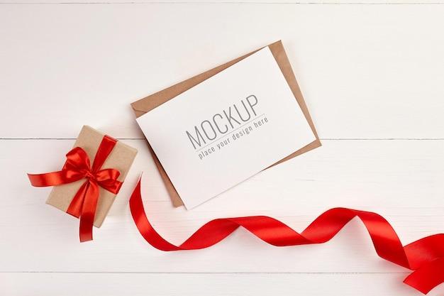 Mockup di biglietto di auguri con confezione regalo e nastro rosso