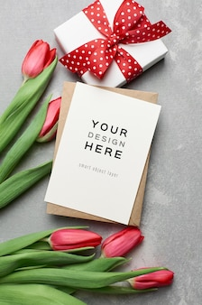 Mockup di biglietto di auguri con confezione regalo e fiori di tulipano rosso