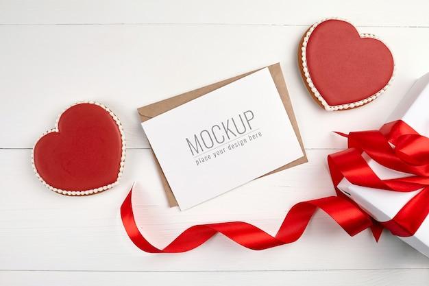 Mockup di biglietto di auguri con confezione regalo e biscotti con cuori dolci