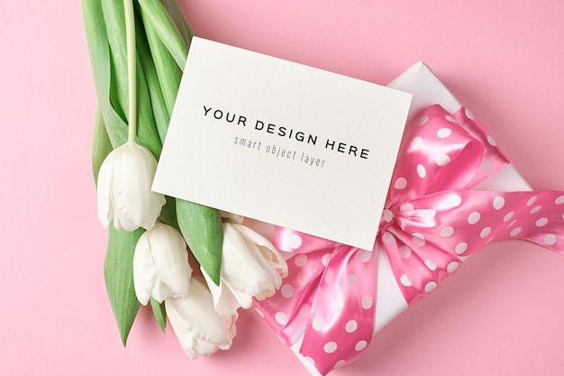 Mockup di biglietto di auguri con confezione regalo e bouquet di fiori di tulipano bianco sul rosa