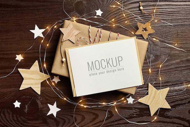 Mockup di biglietto di auguri con confezione regalo, decorazioni in legno e luci natalizie