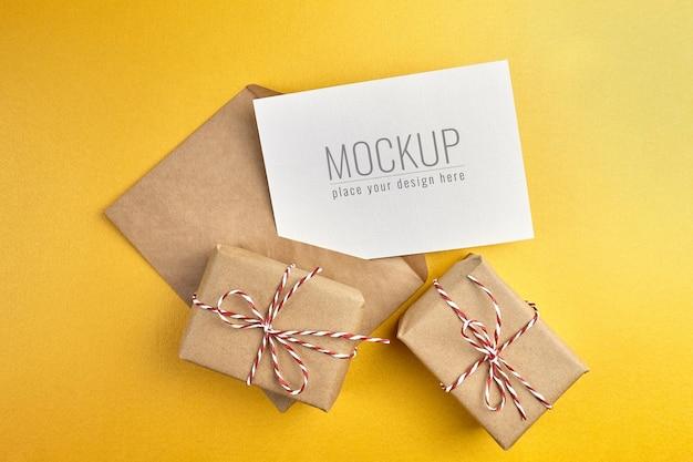 Mockup di biglietto di auguri con scatole regalo su sfondo di carta oro