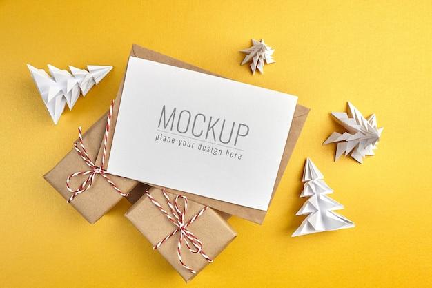 Mockup di biglietto di auguri con scatole regalo e alberi di natale di carta su fondo oro
