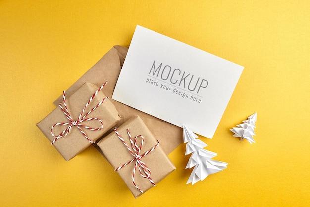 Mockup di biglietto di auguri con scatole regalo e alberi di natale di carta