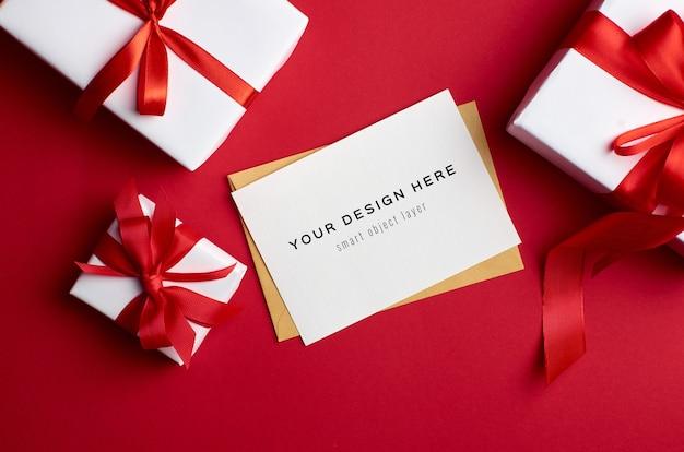 Mockup di biglietto di auguri con scatole regalo su sfondo rosso