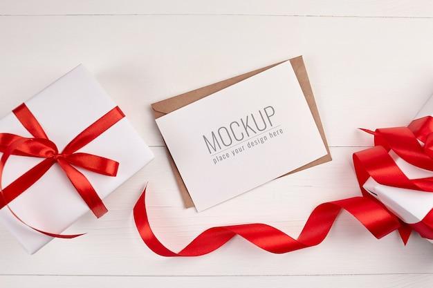 Mockup di biglietto di auguri con scatole regalo e nastro rosso