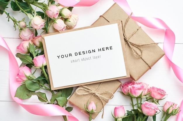 Mockup di biglietto di auguri con scatole regalo e fiori di rose su fondo di legno bianco