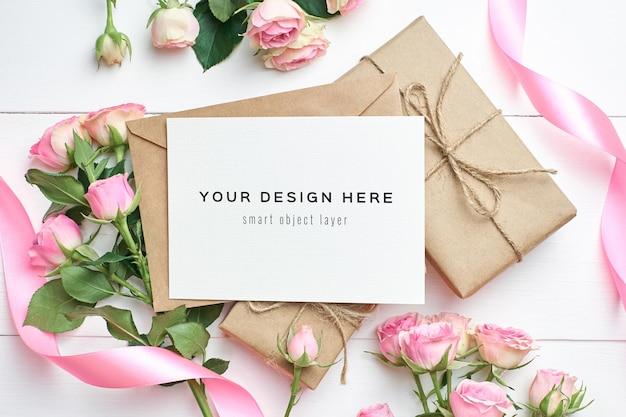 Mockup di biglietto di auguri con scatole regalo e fiori di rose