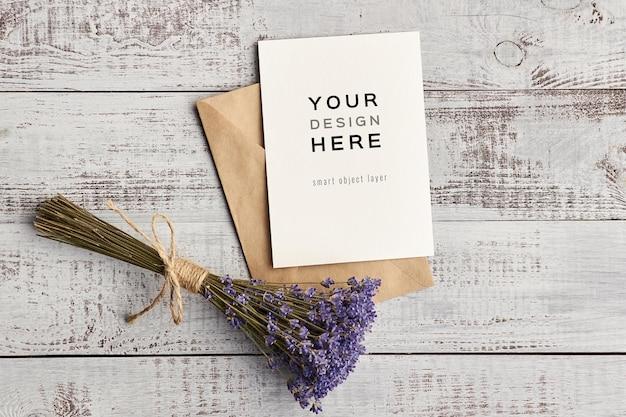 Mockup di biglietto di auguri con fiori di lavanda su fondo in legno