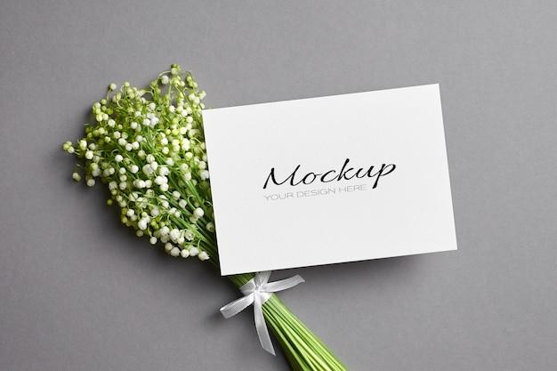 Modello di biglietto di auguri con bouquet di fiori di mughetto su grigio