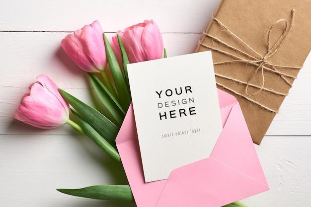 Mockup di biglietto di auguri con busta rosa, confezione regalo e fiori di tulipano