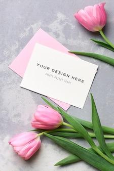 Mockup di biglietto di auguri con busta rosa e bouquet di fiori di tulipano su grigio