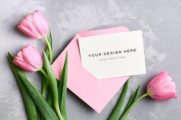 Mockup di biglietto di auguri con busta rosa e bouquet di fiori di tulipano