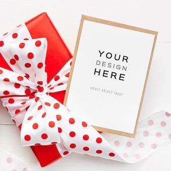 Mockup di biglietto di auguri con confezione regalo rossa con fiocco su sfondo bianco