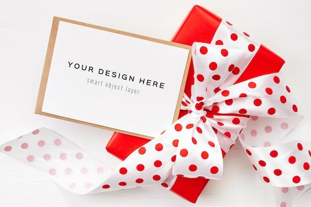 Mockup di biglietto di auguri con confezione regalo rossa con fiocco