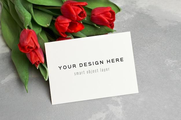 Mockup di biglietto di auguri con bouquet di fiori di tulipano rosso