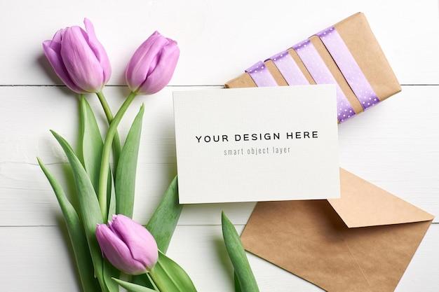 Mockup di biglietto di auguri con fiori di tulipano, busta e confezione regalo