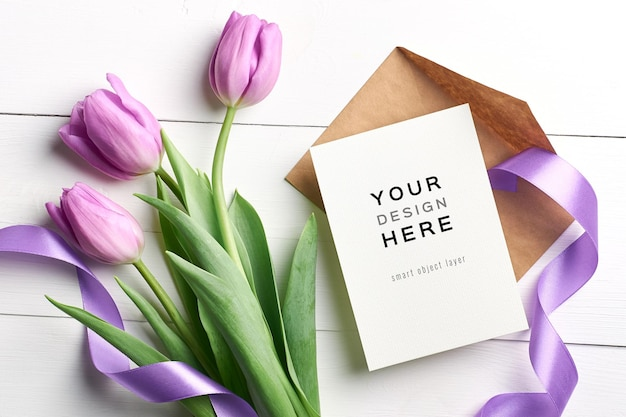 Mockup di biglietto di auguri con fiori di tulipano, busta e nastri su fondo in legno