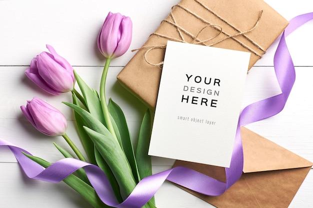 Mockup di biglietto di auguri con fiori di tulipano, confezione regalo e nastri su sfondo bianco