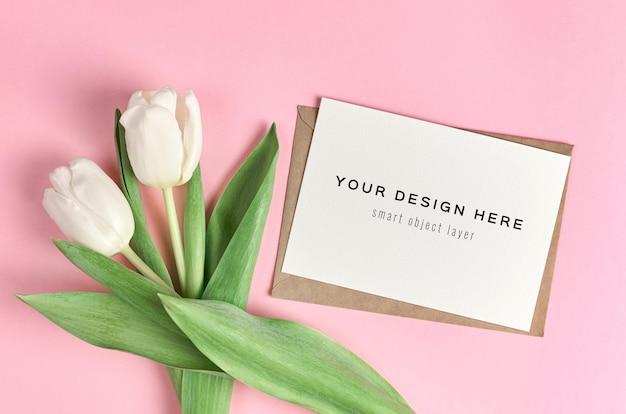 Mockup di biglietto di auguri con bouquet di fiori di tulipano bianco su sfondo rosa
