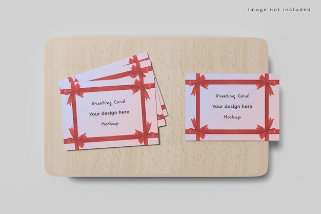 Mockup di biglietto di auguri su tavola di legno isolato